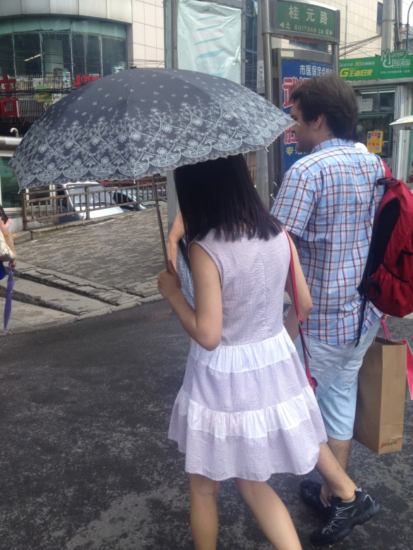 Most of the chinese girls wear and umbrella no matter if it's sunny, cloudy or rainy weather